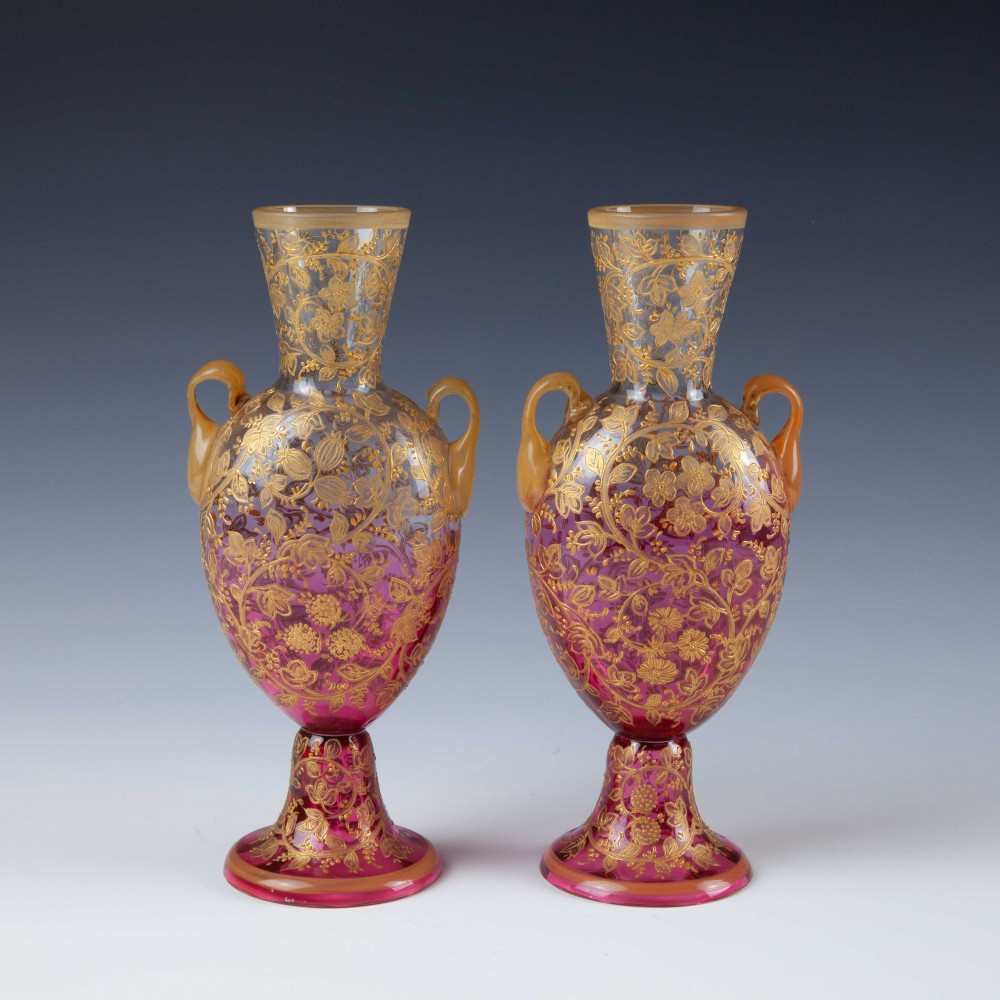 A Pair of Moser / Harrach Cranberry to Clear Gilded Enameled Amphora